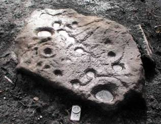 Prehistoric 'cup and ring' rock carvings exposed by fire
