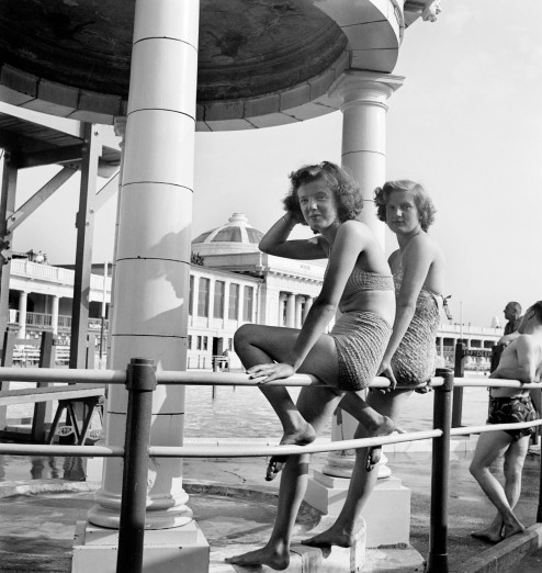 1 AA047938 portrait of two young women in swimming costumes seated on railings beneath diving boards blackpool lido