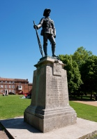 King's Royal Rifle Corps War Memorial, Winchester, Hampshire. Sculpted by John Tweed. Unveiled 26 May 1922. Newly listed at Grade II*. © Historic England DP196436 This memorial by John Tweed, a leading sculptor of his generation, is dramatically sited in Winchester's Cathedral gardens. It honours the 12,840 riflemen who lost their lives in the First World War. The highly realistic bronze figure is of a rifleman in full service dress, with a Lee-Enfield rifle, knapsack and ammunition pouches.