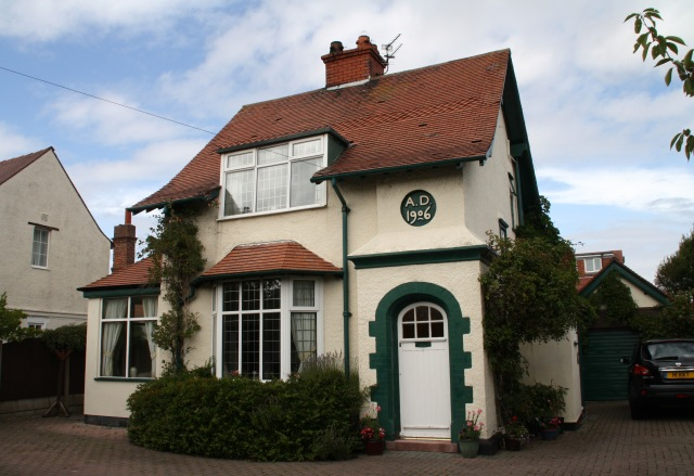 A white wash cottage with dark green drain pipe and brick detailing around the arched front door. A plaque reads AD 1906