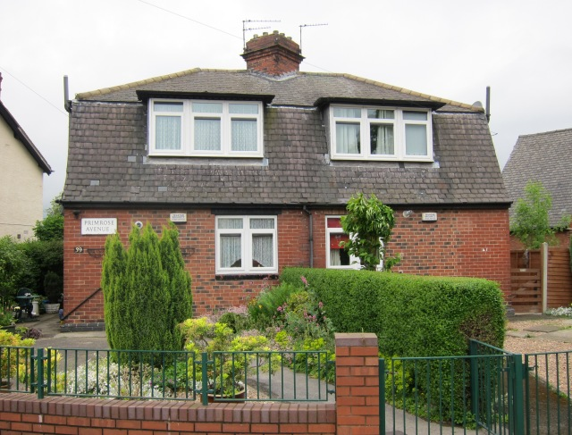 A semi detatched cottage with a well kept garden at the front and a plaque reading 'Primrose Avenue'