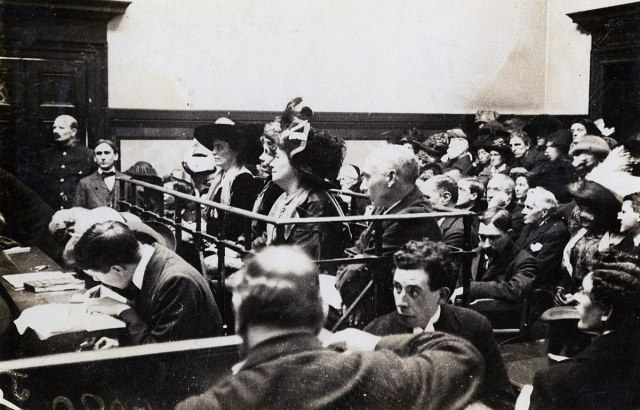 Frederick and Emmeline Pethick Lawrence, Emmeline Pankhurst and (Mabel Tuke) in court, 1912 via Wikipedia