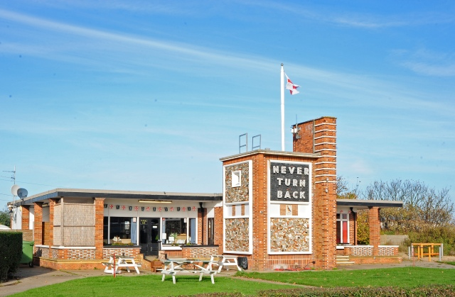 Exterior image of The Never Turn Back pub, a brick building with a union jack flag flying from a flag pole