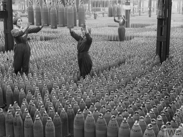 Female Chilwell munitions workers lower 6-inch howitzer shells into position