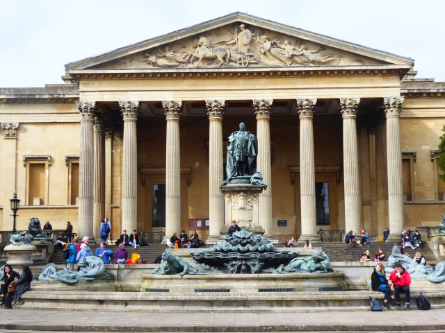 Exterior image of the Victoria rooms in Bristol, with people sat outside eating lunch