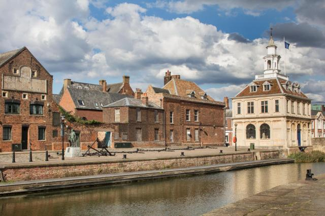 A row of historic buildings seen across a river