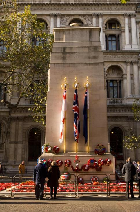 Cenotaph memorial surrounded by wreaths with three people stood behind a protective barrier
