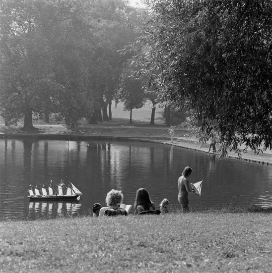 A couple lie on the grass watching a child sail boats at highgate ponds, hampstead, london