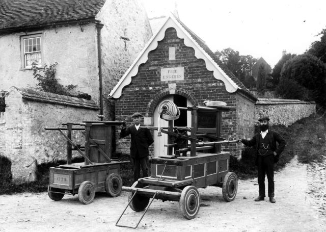 Two men standing with two fire engines outside the Fire Station on The Green in Aldbourne, Wiltshire