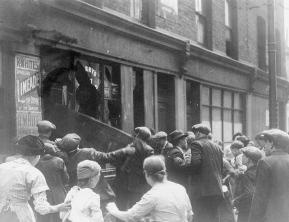 Crowds of rioters breaking the windows of a shop