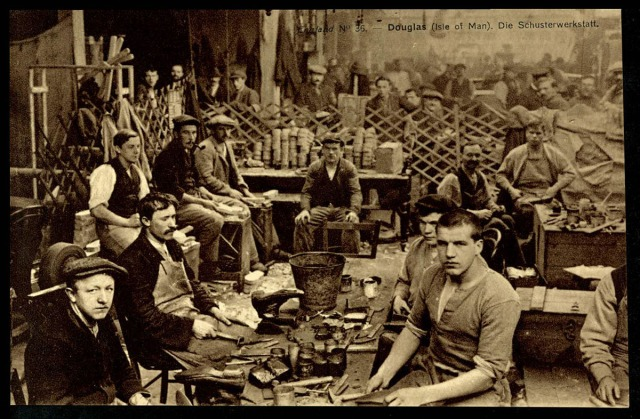 POWs sit in a cobblers workshop, surrounded by materials - their expressions are solemn