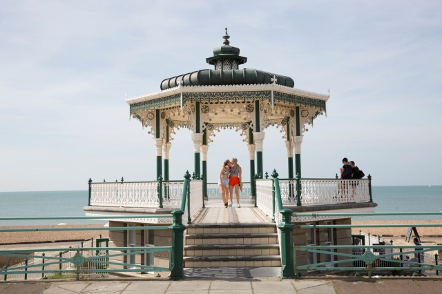 A young couple kiss, framed by Brighton's birdcage bandstand during Pride weekend
