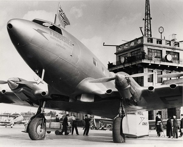 DH91 aircraft seen in front of the airport building, with passengers and staff in the background