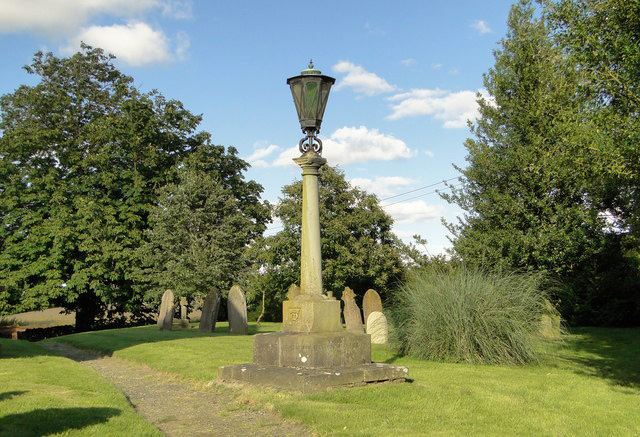 A stone memorial, topped by a lantern, in St Mary the Virgin churchyard.