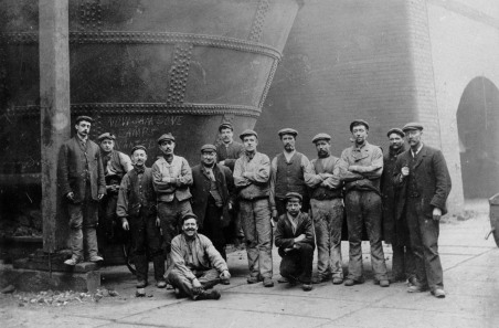 Bolckow Vaughan blastfurnacemen pose for a photograph in front of their blast furnace at Middlesbrough. Early 20th Century