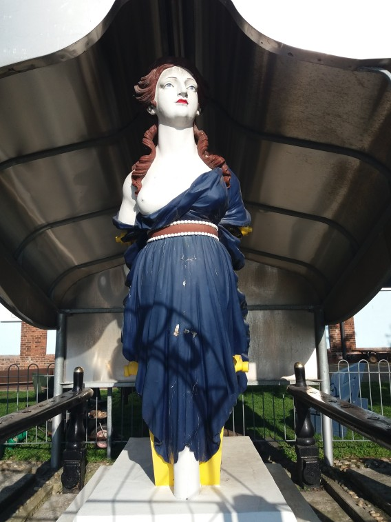 Figurehead of a woman with brown hair and one bare breast