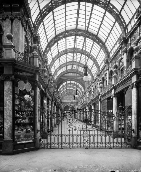 Entrance to arcade with closed iron gates and plate glass roof visible