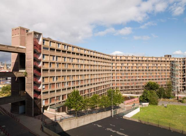 Wide image of large block of flats in two sections, facing green space