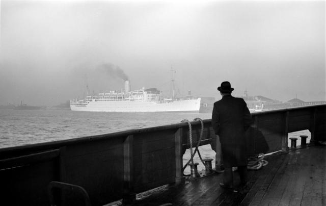 A man on an ocean liner looks on at another moored liner at Tilbury Passenger Landing Stage