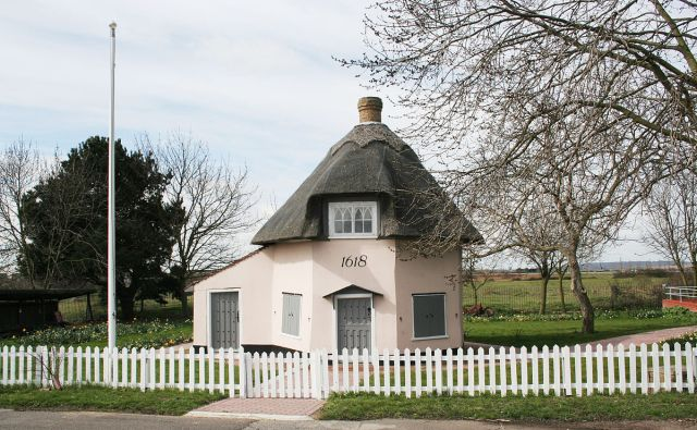 A small, light pink octagonal cottage with a thatched roof. The painted date above the grey front door reads '1618'